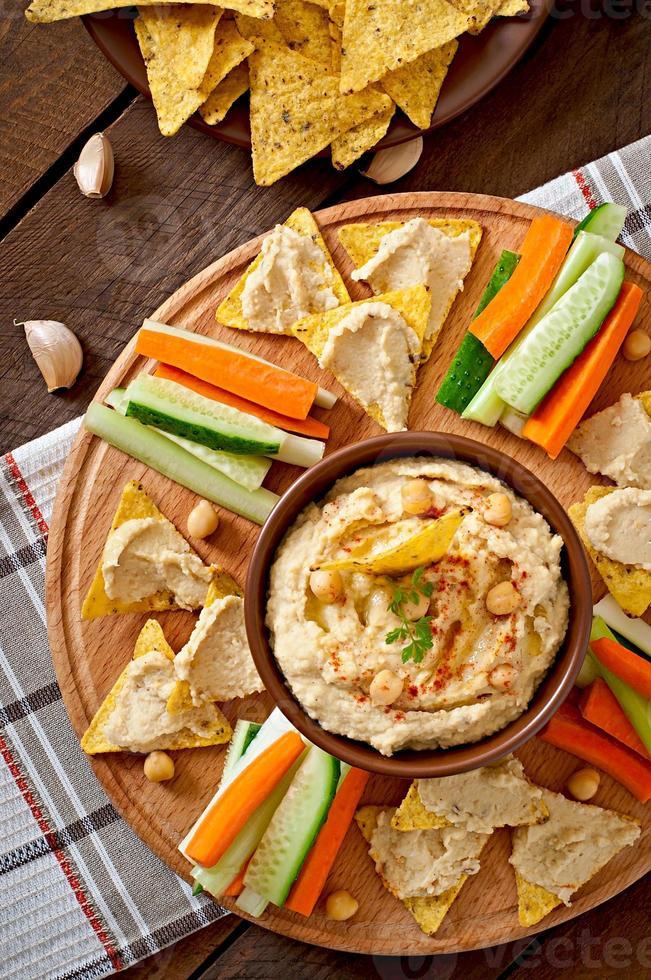 gesunder hausgemachter Hummus mit Gemüse, Olivenöl und Pita-Chips foto