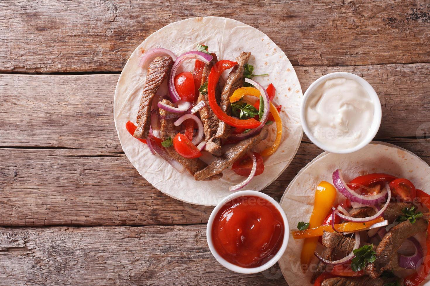 Tortillas mit Fleisch, Gemüse und Soße horizontale Draufsicht foto
