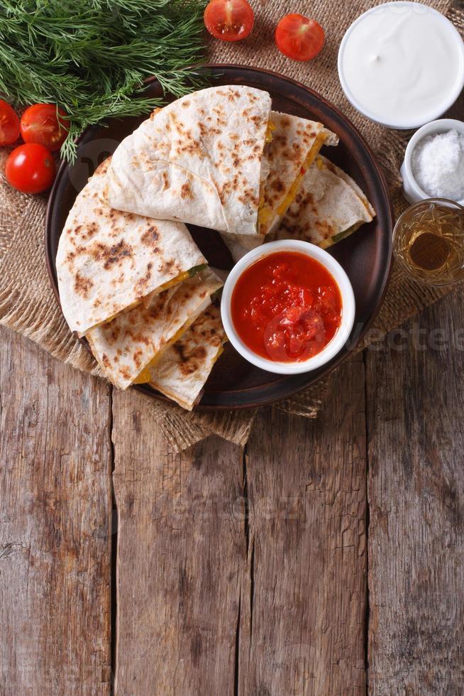 Quesadilla in Scheiben geschnitten und Saucen auf einem Teller. vertikale Draufsicht foto