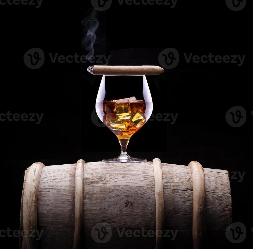Cognac und Zigarre auf Schwarz mit Vintage-Fass foto