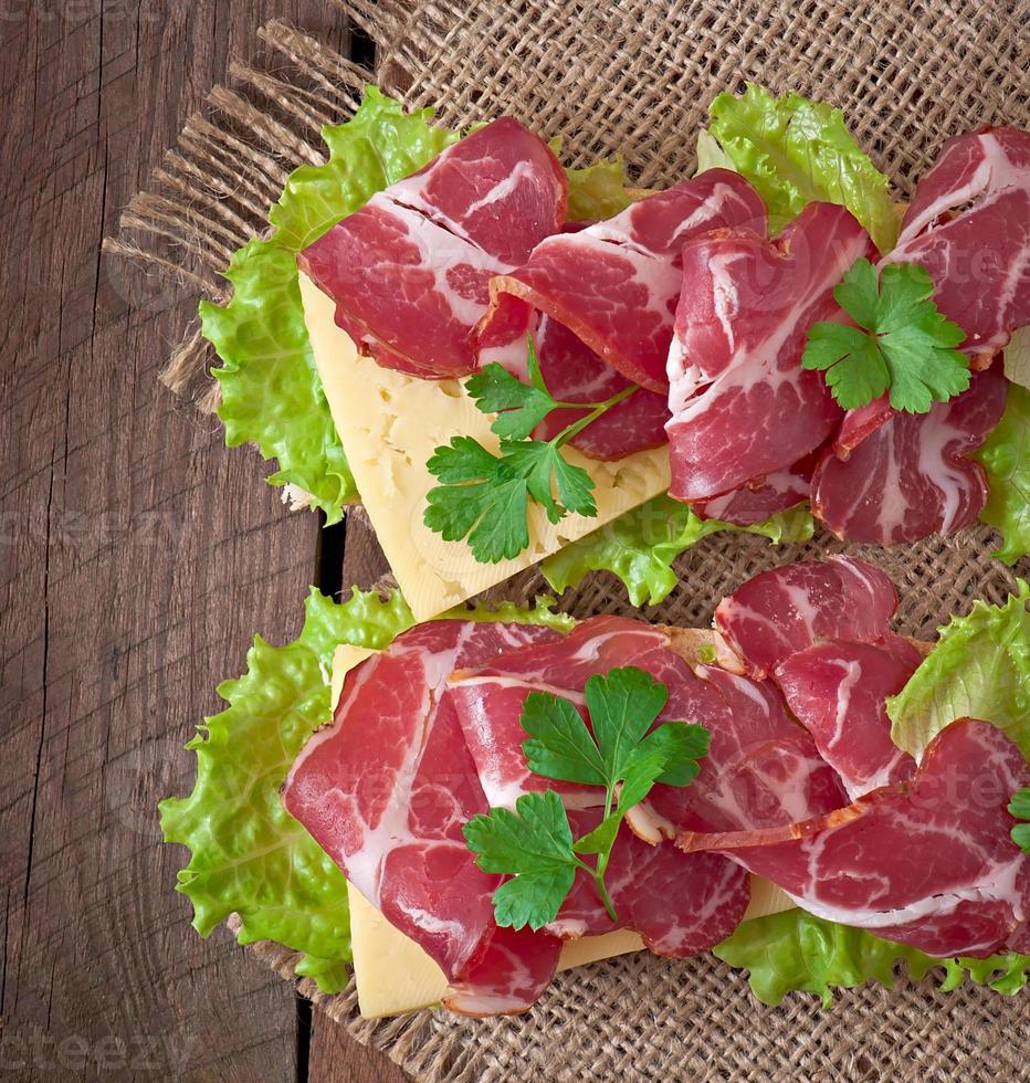 großes Sandwich mit rohem geräuchertem Fleisch auf einem hölzernen Hintergrund foto