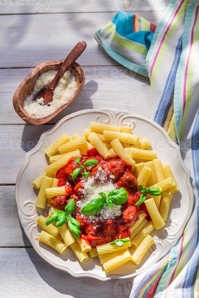 hausgemachte Pasta Penne mit Tomaten, Basilikum und Parmesan foto