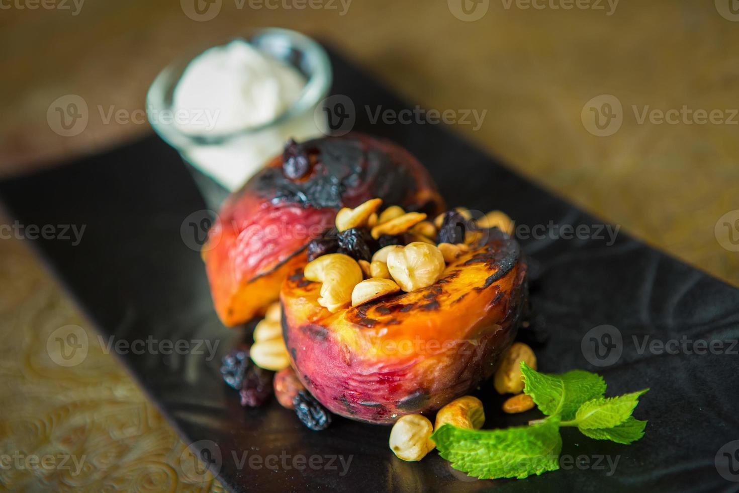 Gegrillte Pfirsiche mit Nüssen und Eis foto