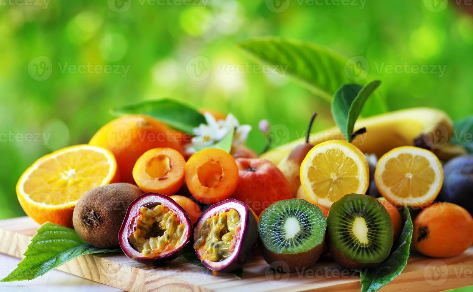 Früchte mit Blättern auf Tabelle auf grünem Hintergrund foto