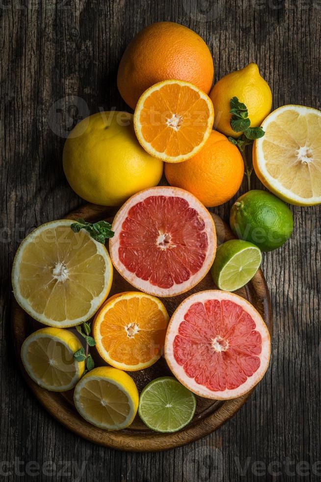 frische Zitrusfrüchte auf rustikalem hölzernem Hintergrund, Draufsicht foto