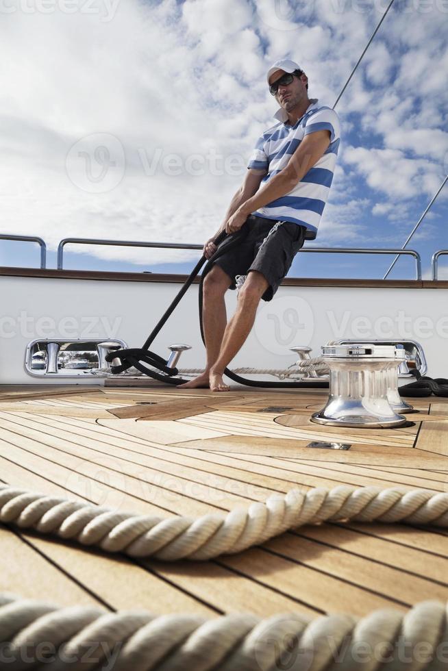 dynamischer Segler an Bord der Yacht, der die Seile festzieht foto