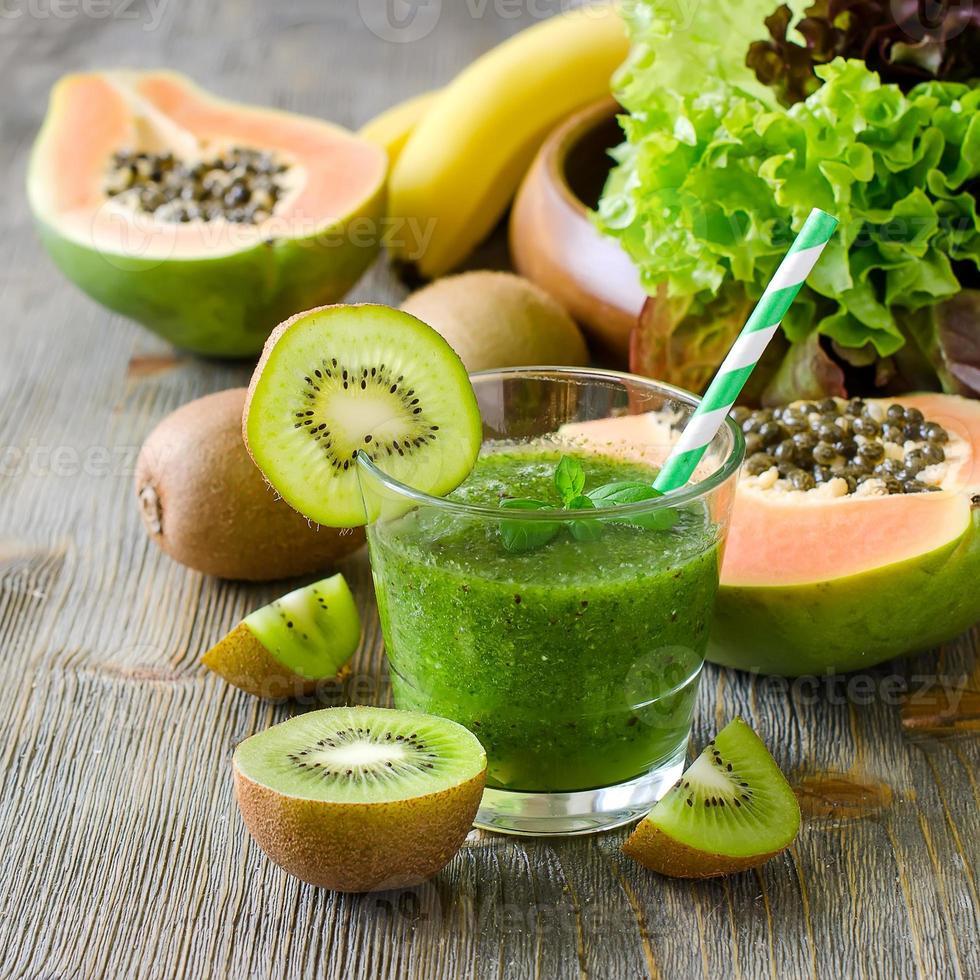 grüner tropischer Smoothie mit Kiwi, Papaya und Salatblättern foto