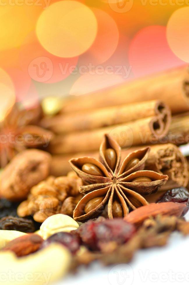 Weihnachtsgewürze, Nüsse, Kekse und getrocknete Früchte auf Bokeh-Hintergrund foto