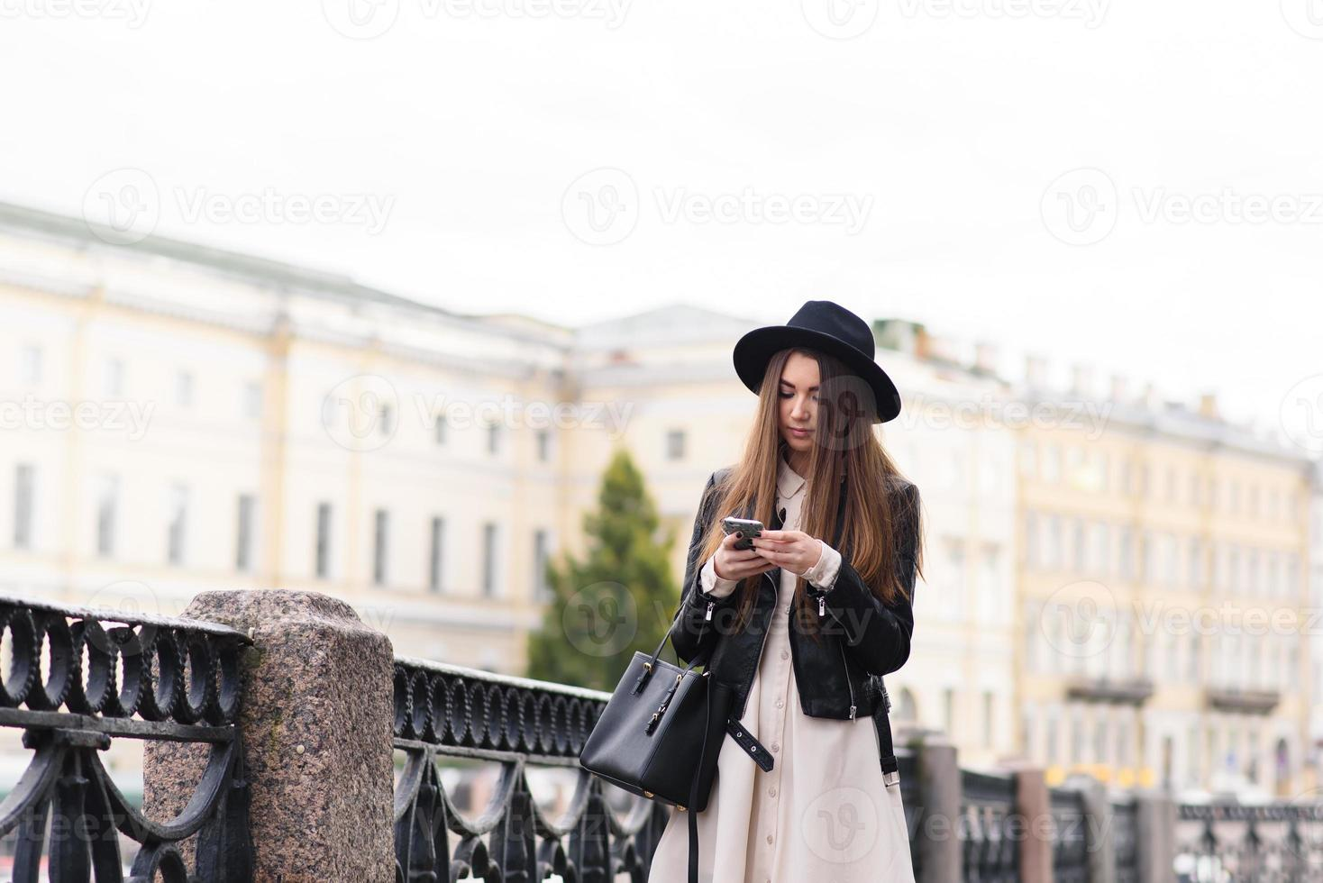 modische weibliche Lesemeldung auf Handy während des Spaziergangs draußen foto