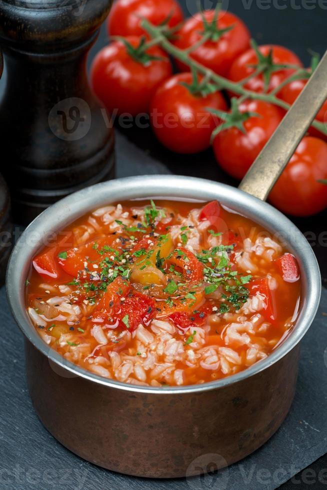 würzige Tomatensuppe mit Reis, Gemüse, Kräutern in einem Topf foto