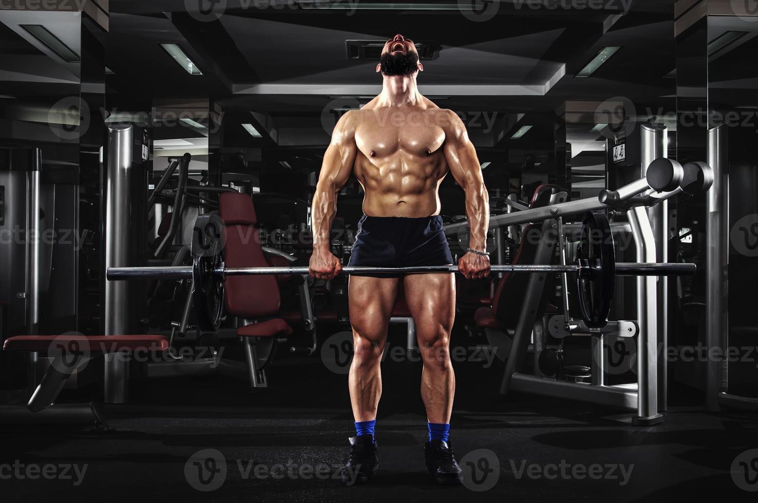 muskulöser Mann, der einige schwere Hanteln anhebt foto