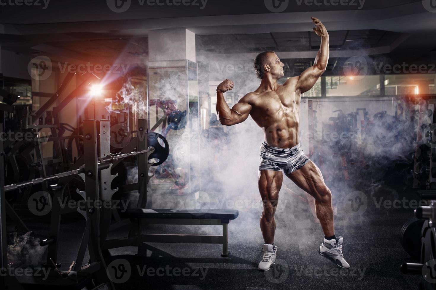 Bodybuilder-Mann, der im Fitnessstudio aufwirft foto