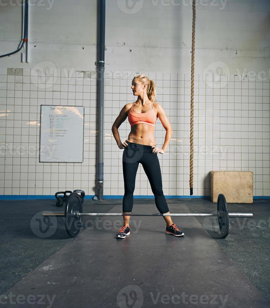 fit junge Frau im Fitnessstudio mit Langhantel foto
