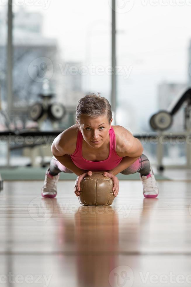 junge Frau, die Liegestütze auf Medizinball ausübt foto