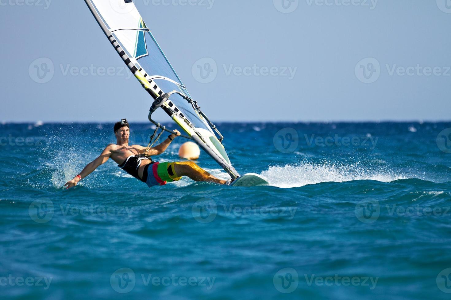 junger Mann, der den Wind in Wasserspritzern surft foto