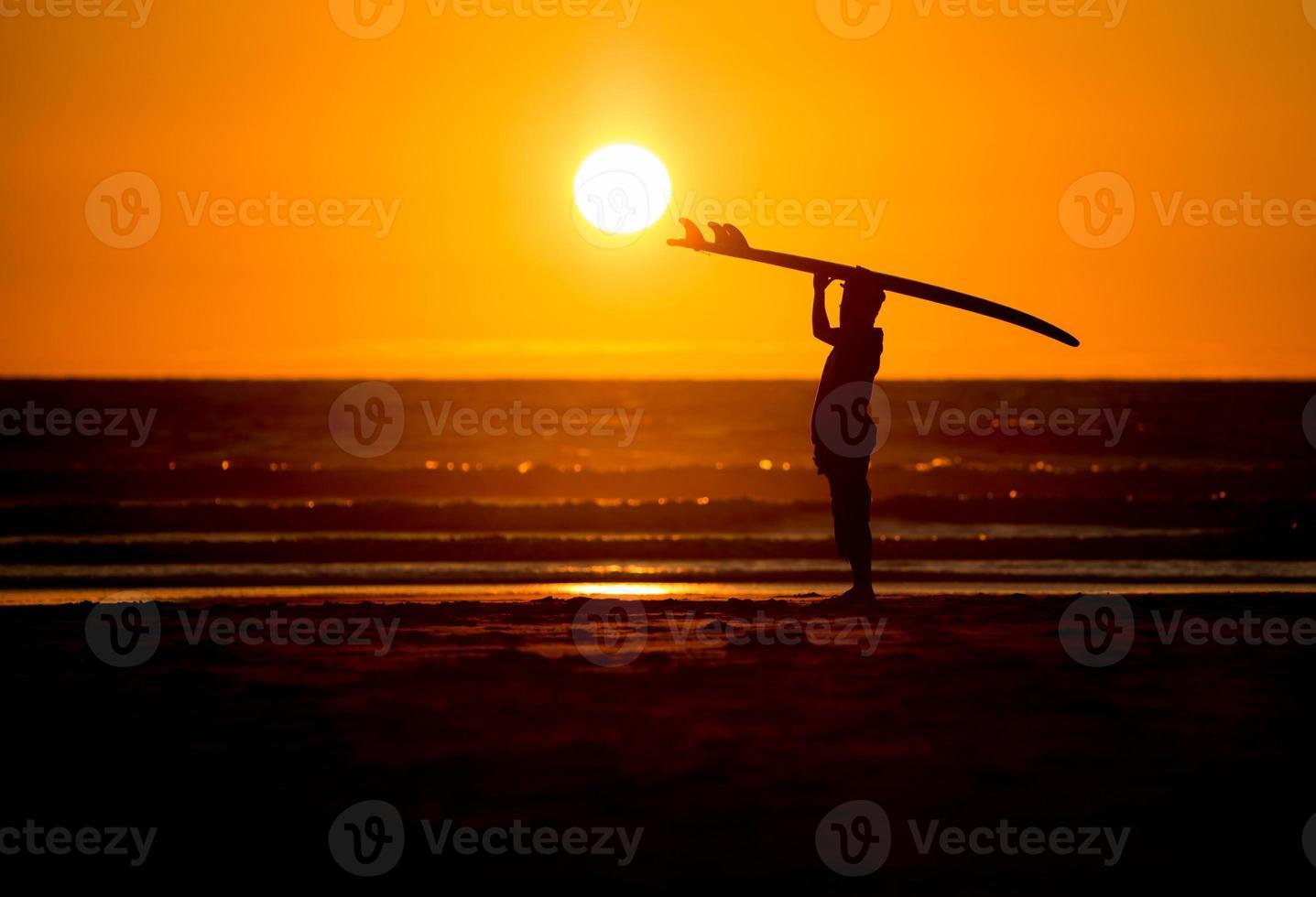 Mann mit Surfbrett im Sonnenuntergang am Strand foto