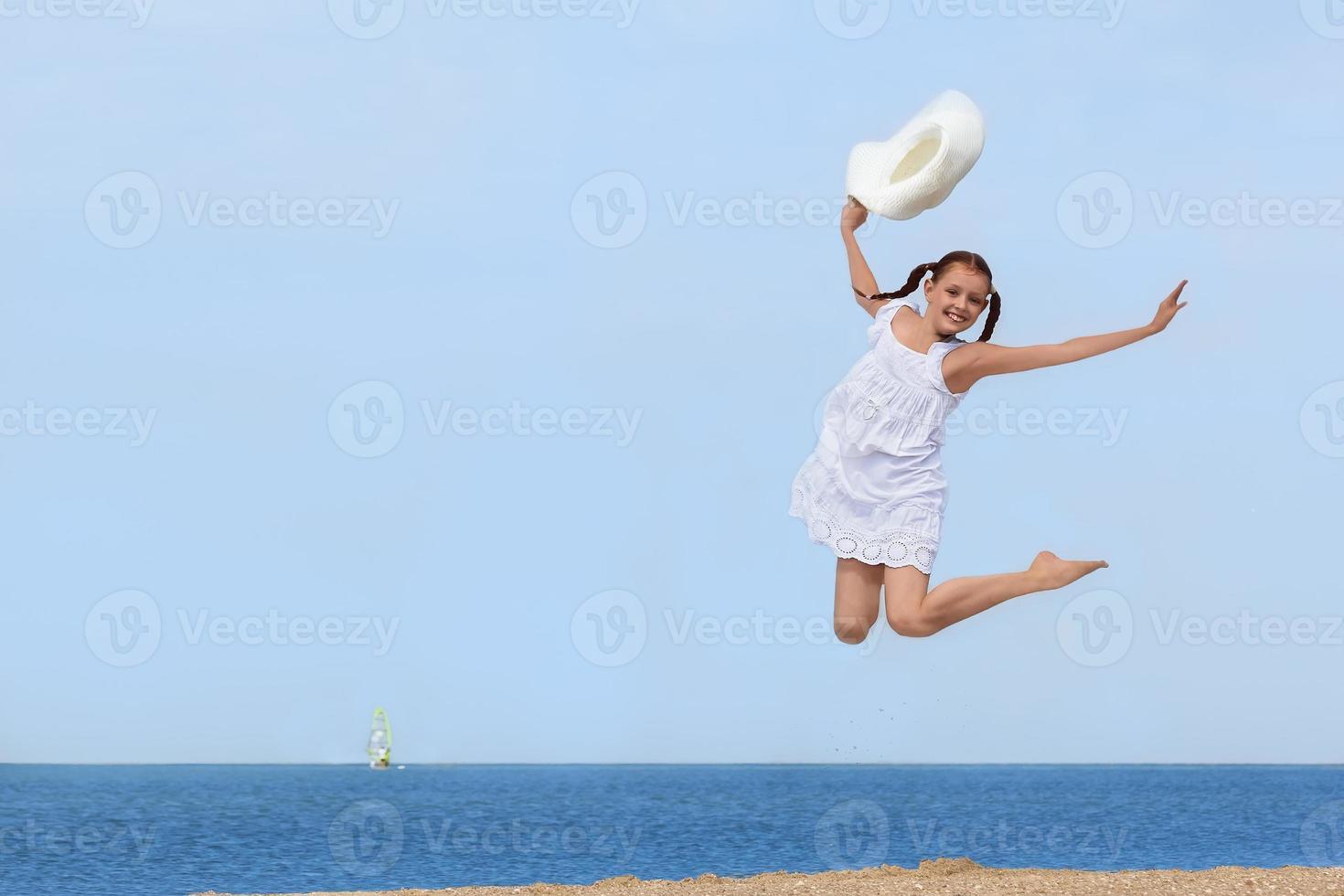 fröhliches Mädchen, das über das Wasser am Strand springt foto