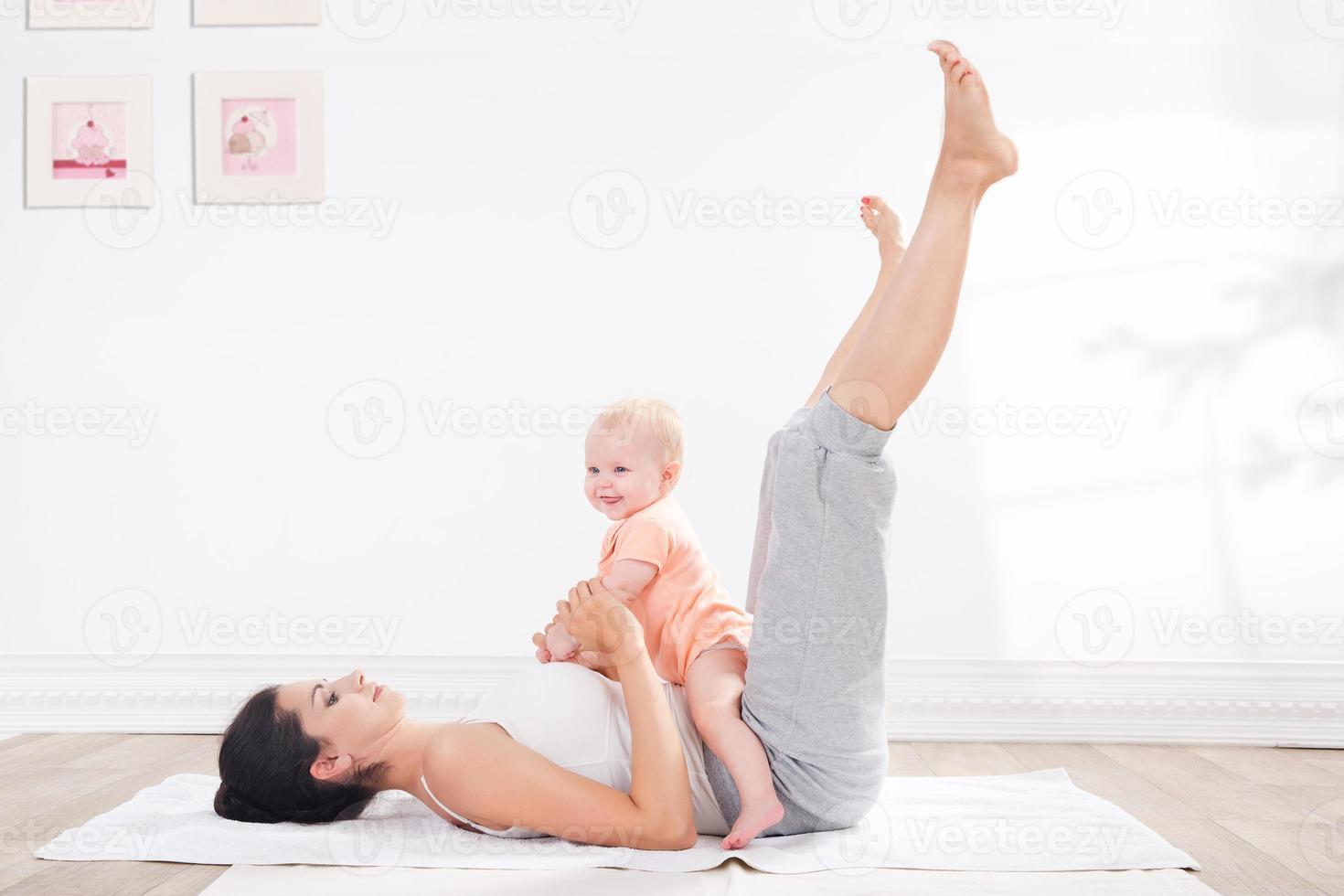 Mutter macht Gymnastik mit ihrem Baby foto
