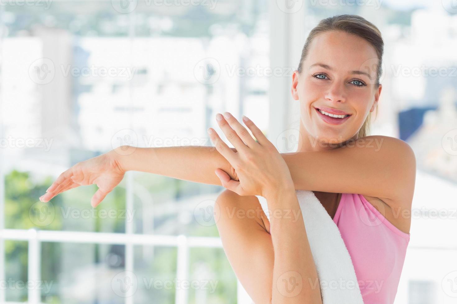 sportliche junge Frau, die Hände im Yoga-Kurs streckt foto