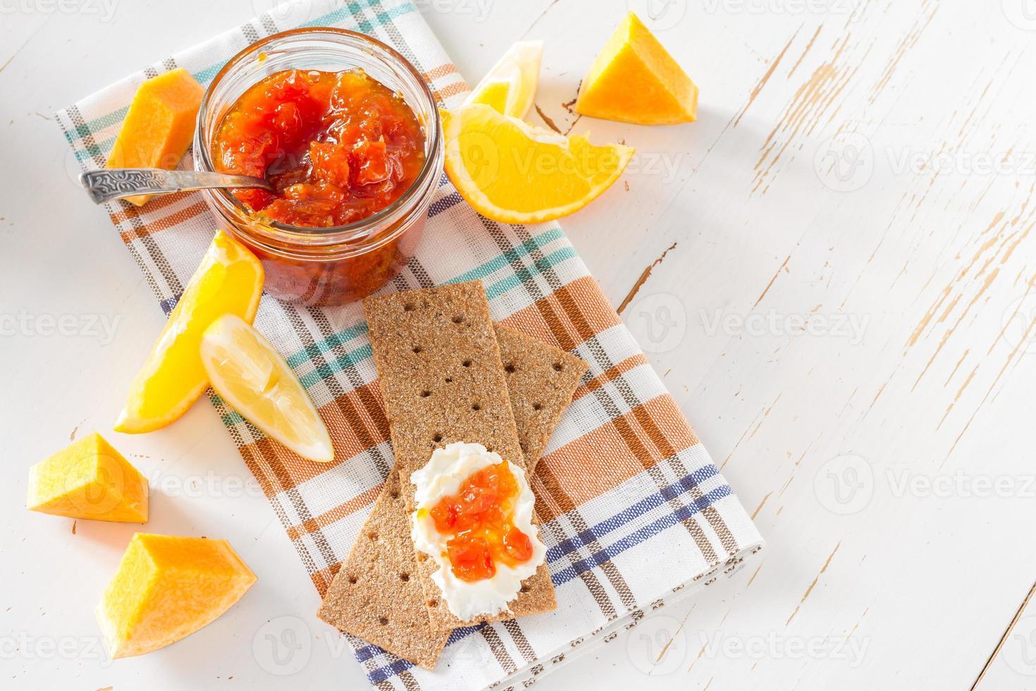 Marmelade im Glas mit Zutaten und knusprigem Brot foto