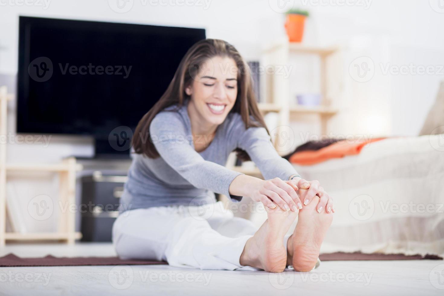 Frau macht Fitness zu Hause im Wohnzimmer foto
