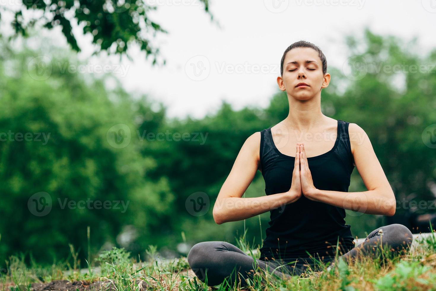 Frau, die im Lotussitz draußen sitzt foto