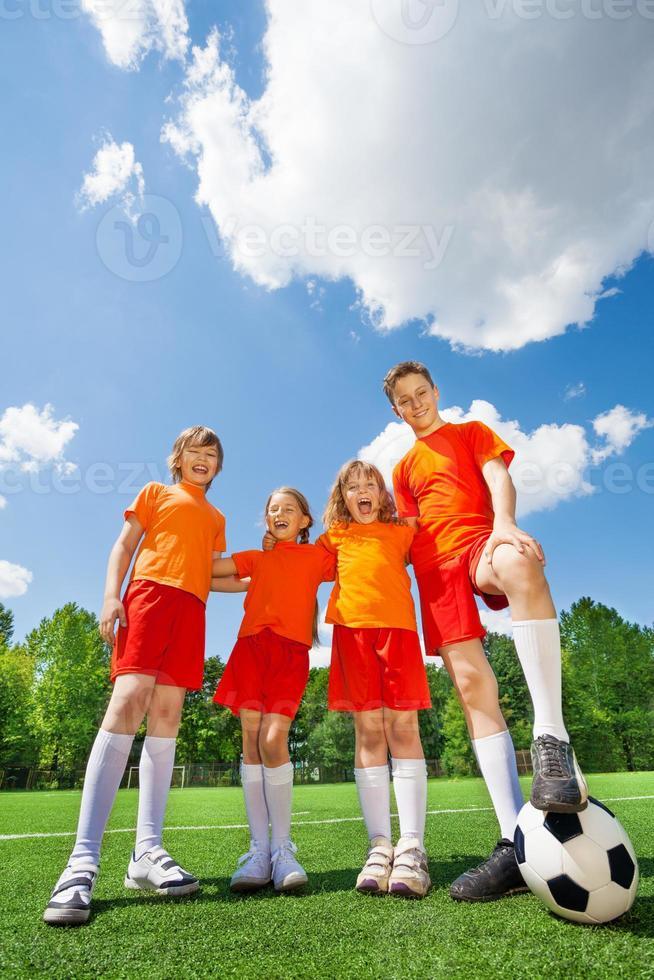 Kinder unterschiedlicher Größe mit Fußball in Reihe foto