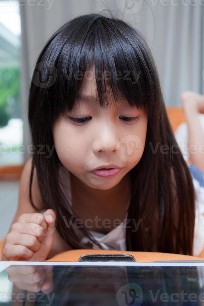 Mädchen spielt mit Tablette. foto