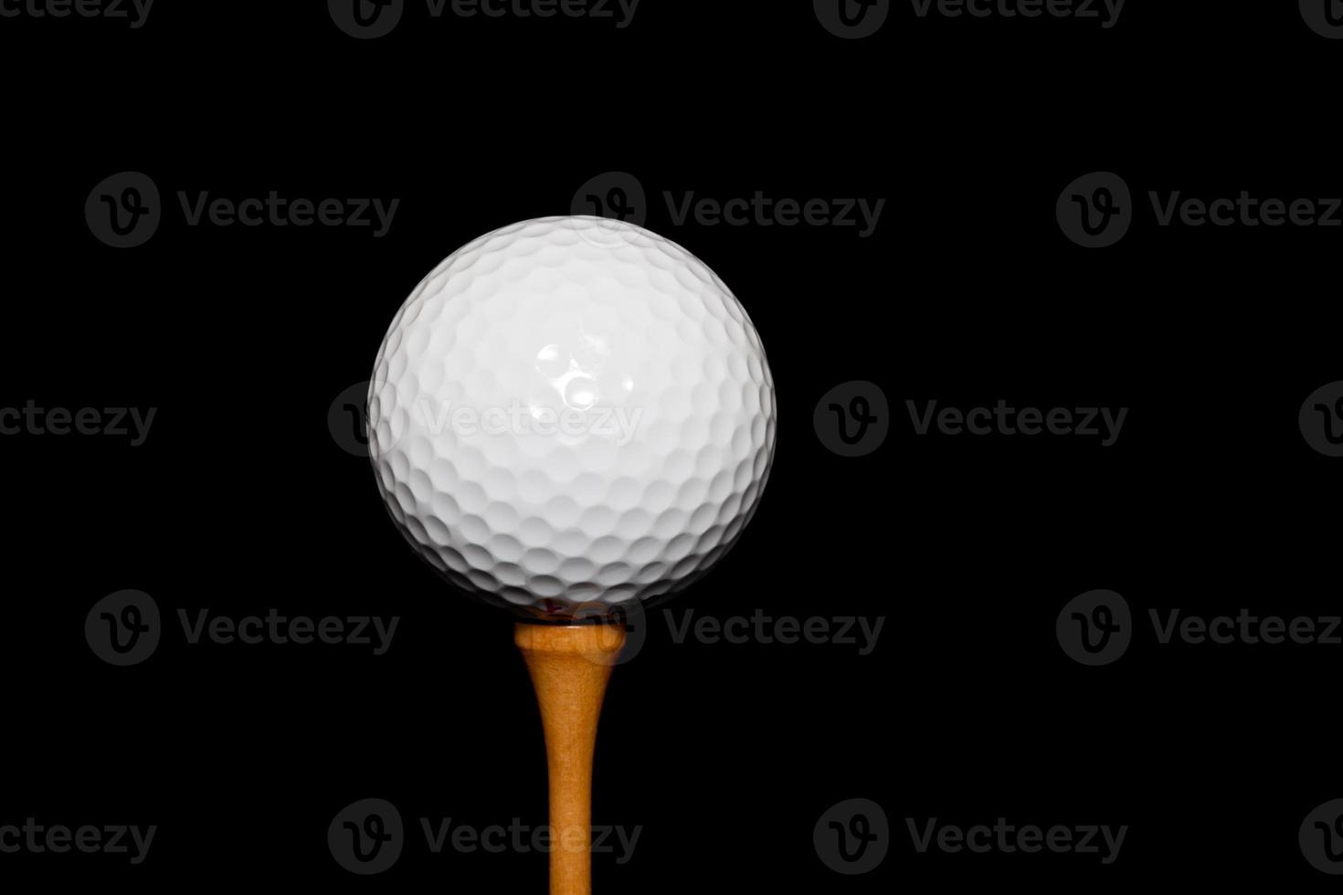Golfball auf Abschlag auf schwarzem Hintergrund foto