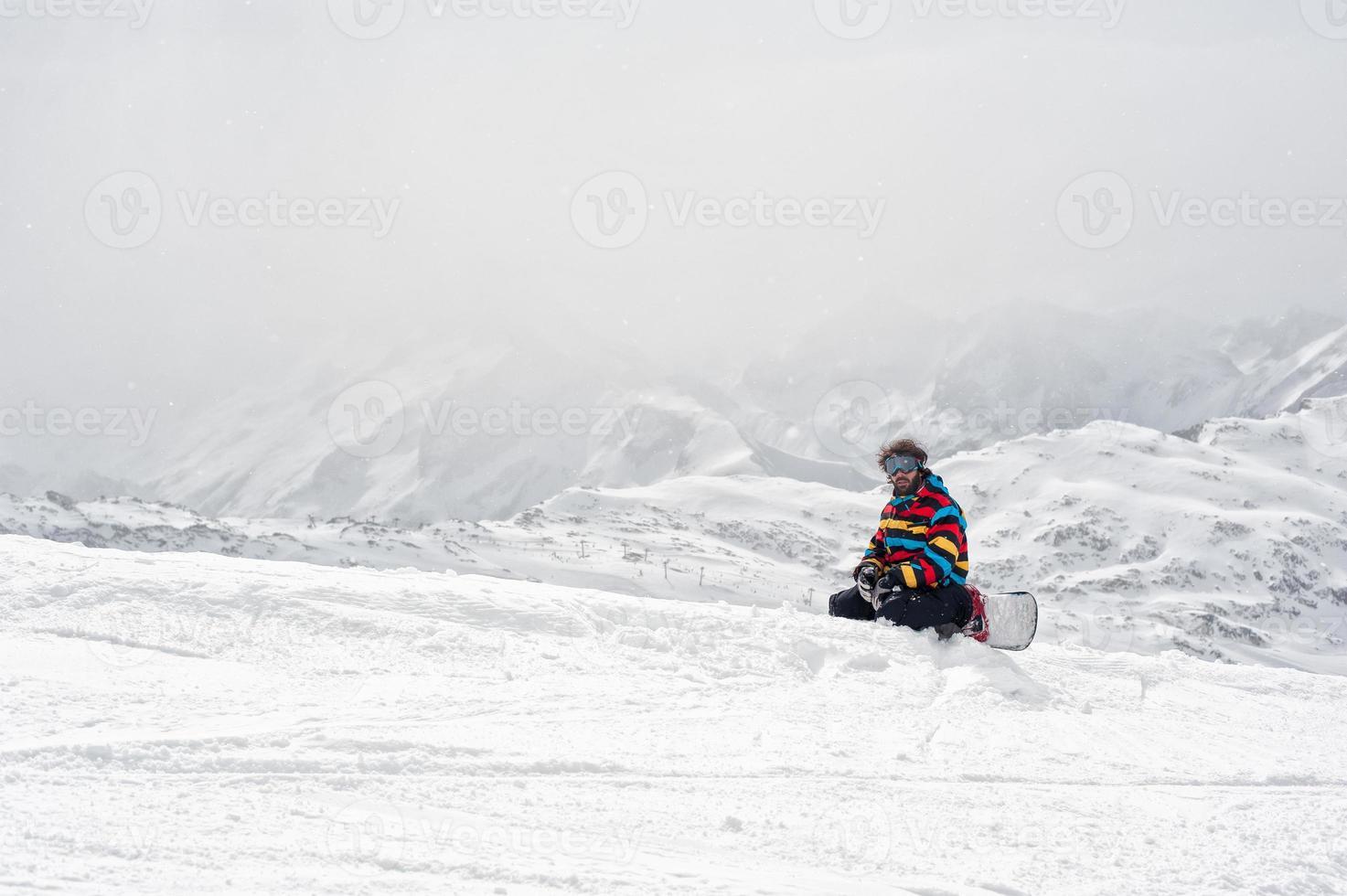 Snowboarder sitzen oben auf dem Berg foto