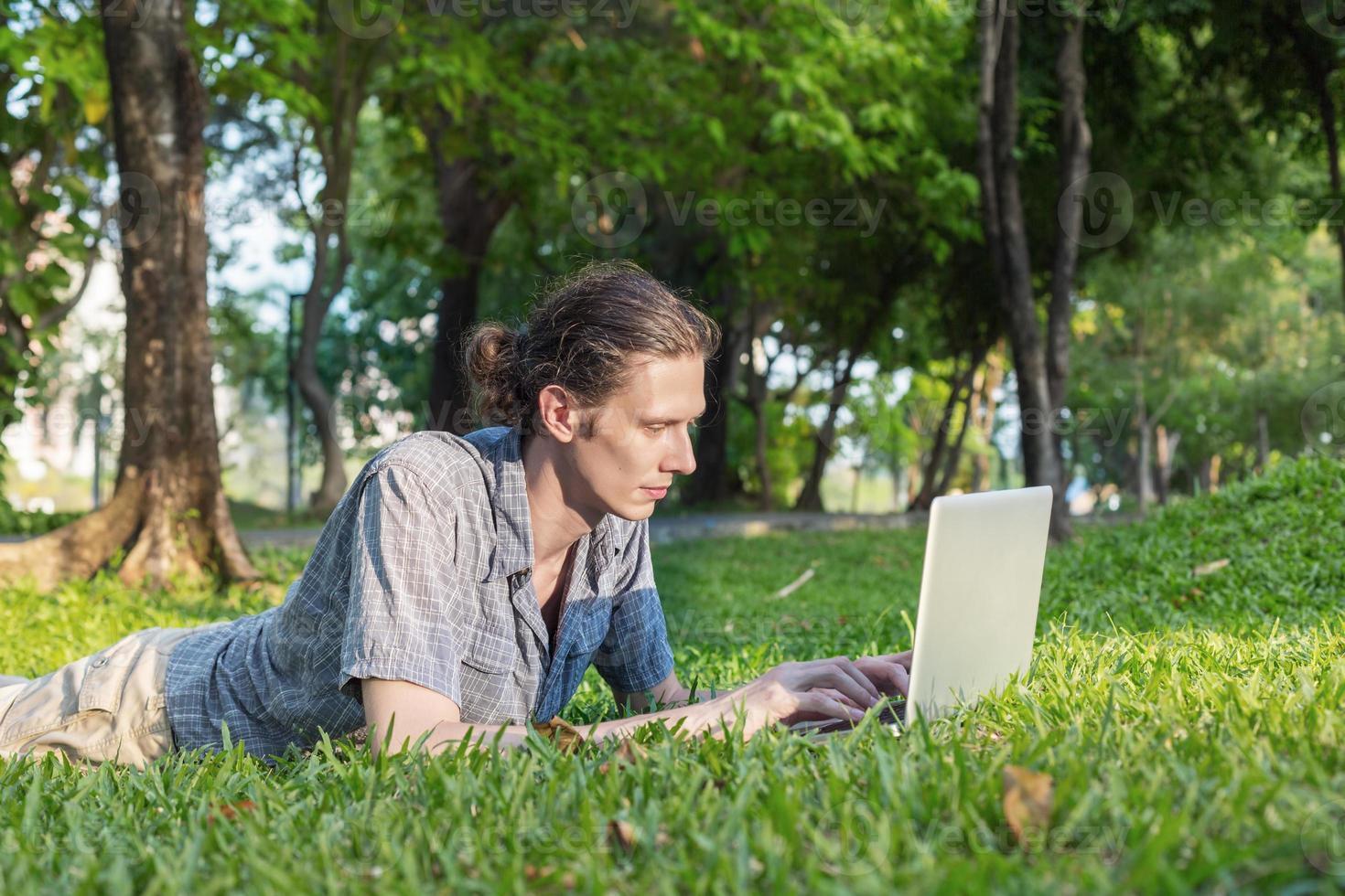 Yang Geschäftsmann arbeitet im Freien mit Laptop-Computer foto