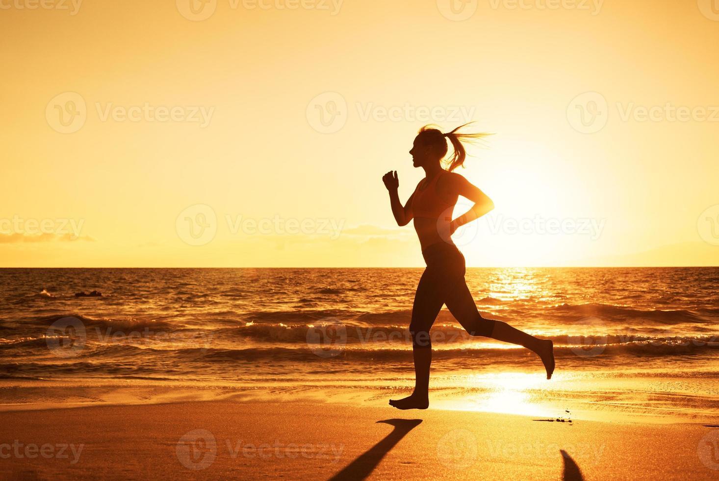 Frau läuft bei Sonnenuntergang foto
