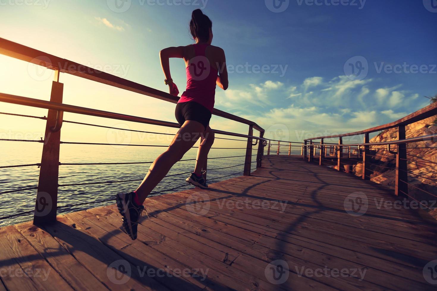 Beine der jungen Fitnessfrau, die auf hölzerner Promenade am Meer laufen foto