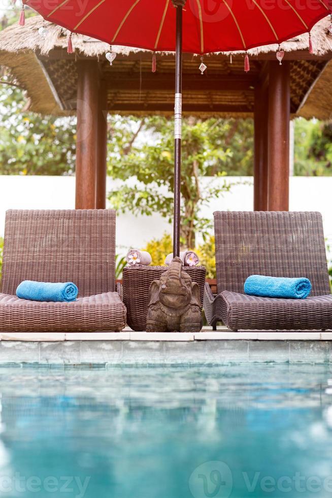 Liegestühle in der Nähe von Schwimmbad foto