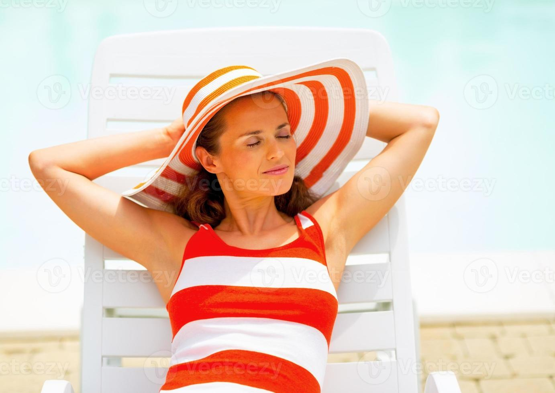 entspannte junge Frau, die auf Chaiselongue liegt foto