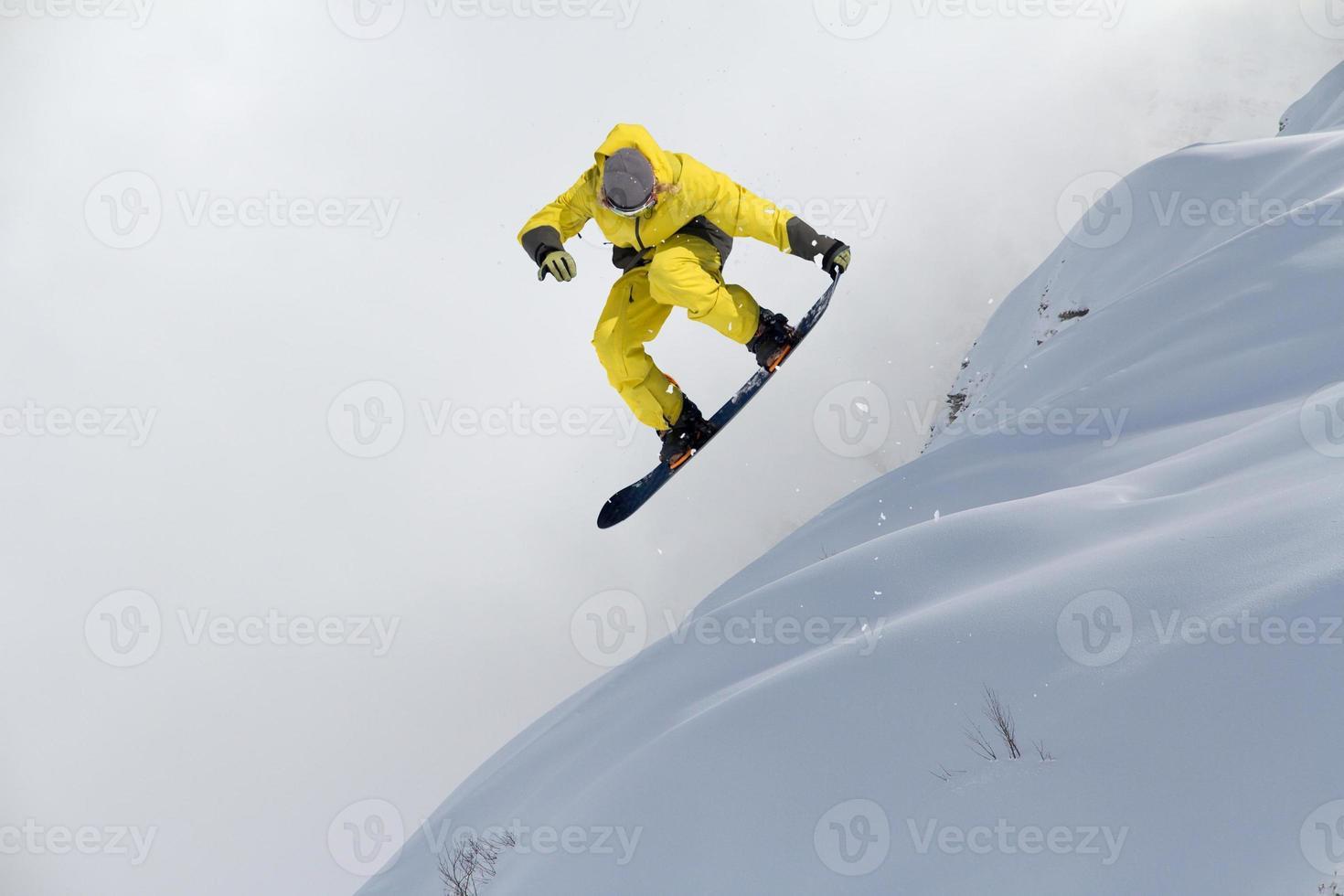 fliegender Snowboarder auf Bergen. Extremsport foto