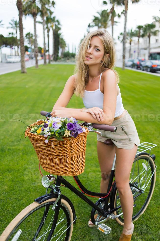 junge charmante Radfahrerin, die mit ihrem Vintage-Fahrrad draußen aufwirft foto
