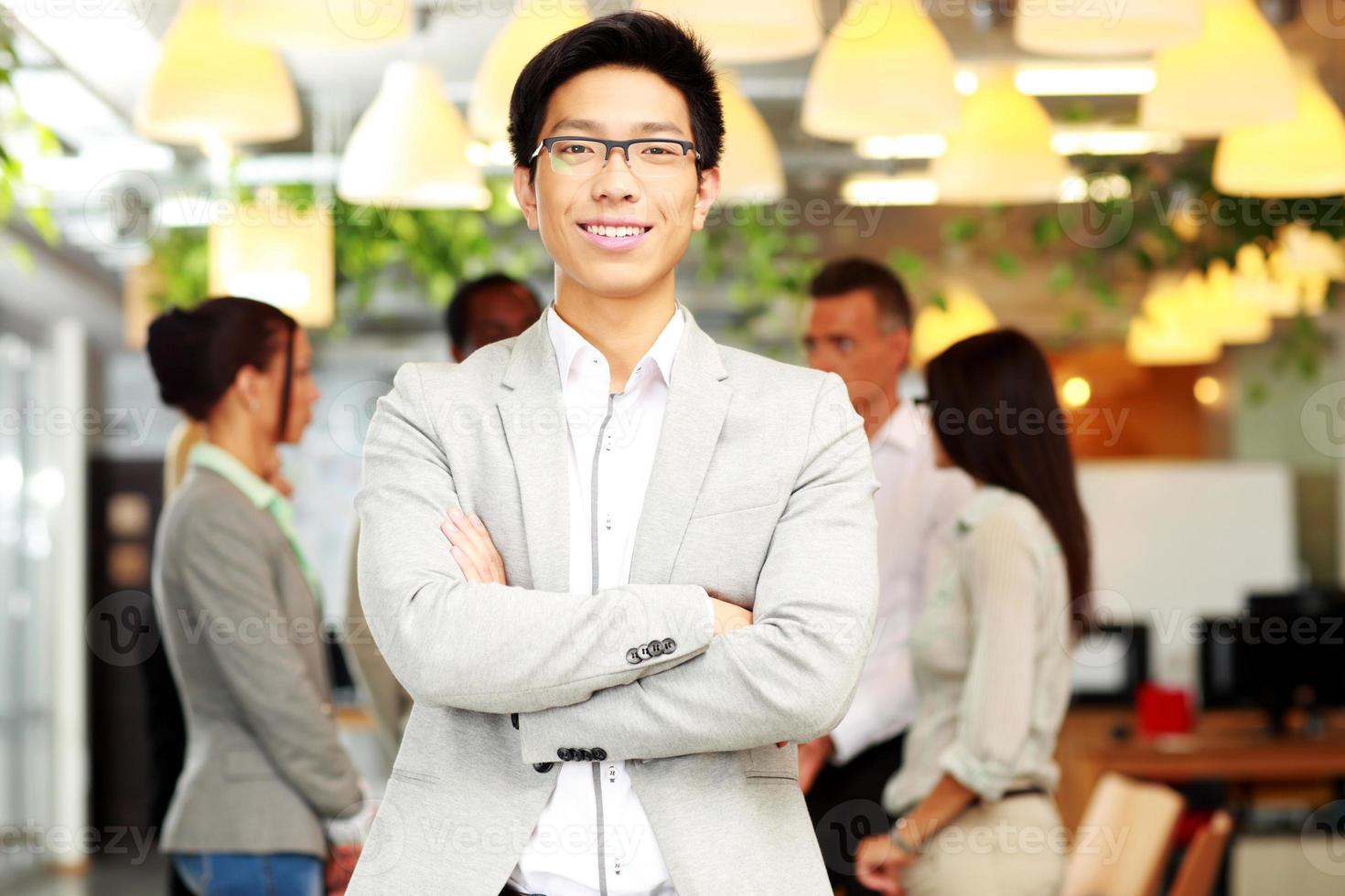 Porträt des lächelnden Geschäftsmannes mit verschränkten Armen foto