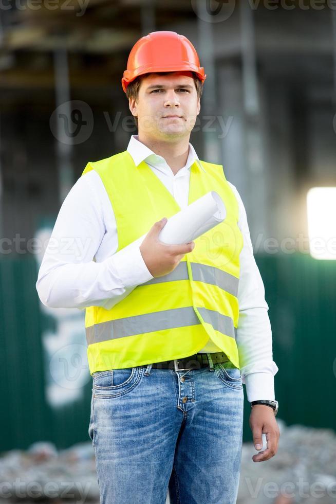 Architekt im Helm posiert mit Blaupausen gegen Gerüste foto
