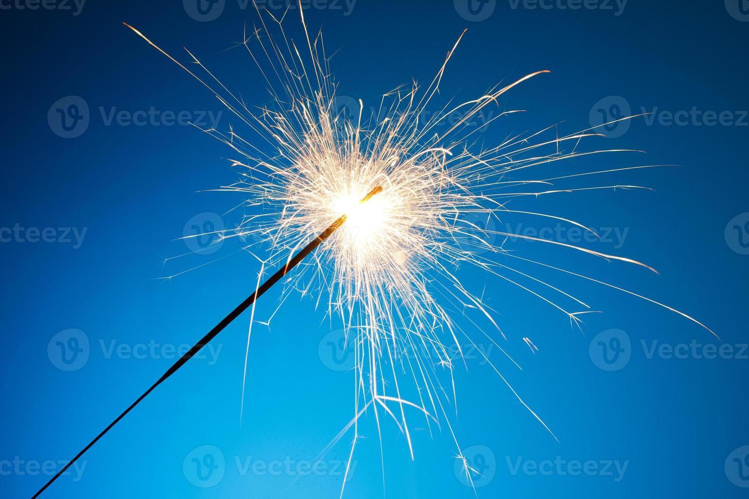 frisch beleuchtete Wunderkerze auf blauem Hintergrund foto