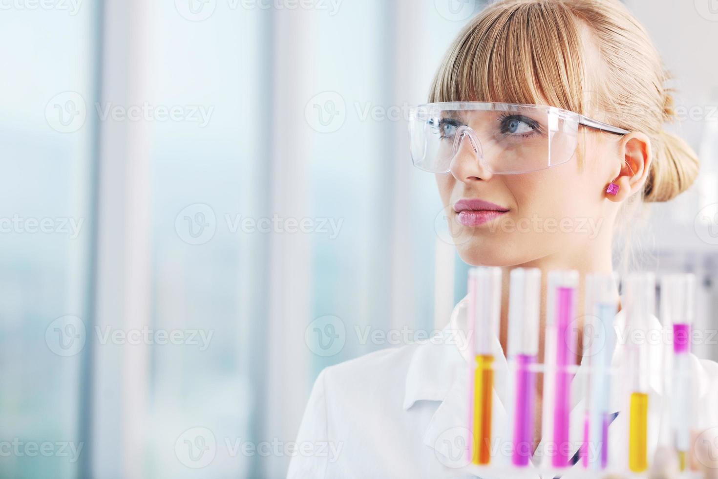 Forscherin hält ein Reagenzglas im Labor hoch foto