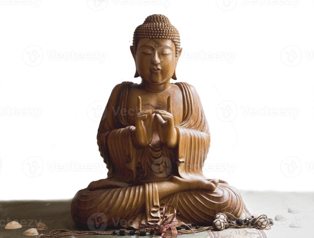 Holzbuddha in der Meditation lokalisiert im weißen Hintergrund foto