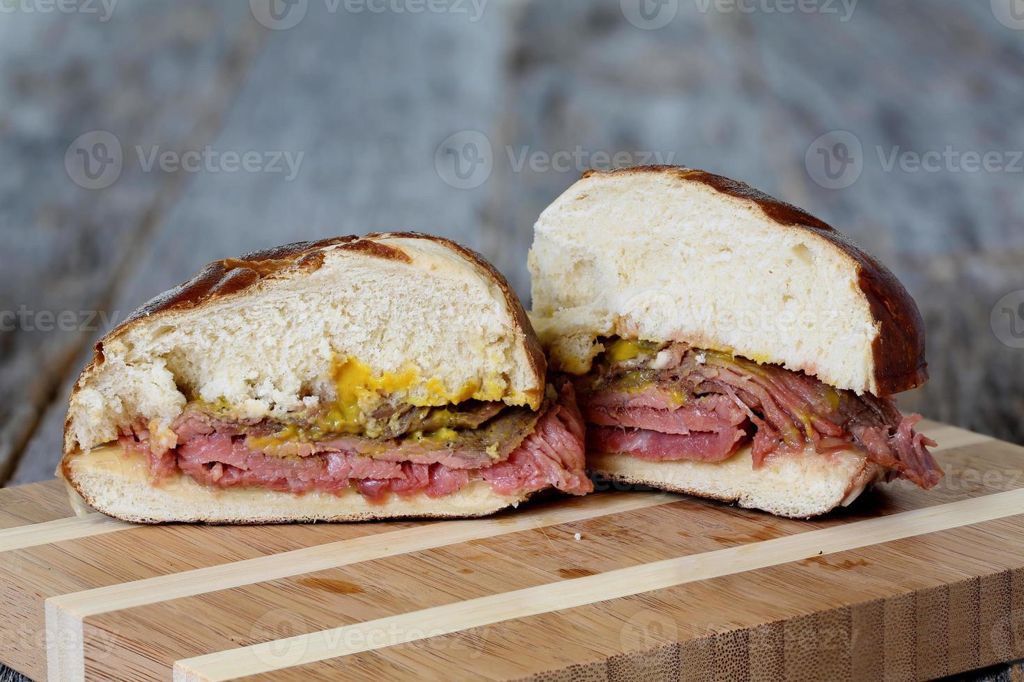Flankensteak-Sandwich mit Brezelbrötchen und Senf foto