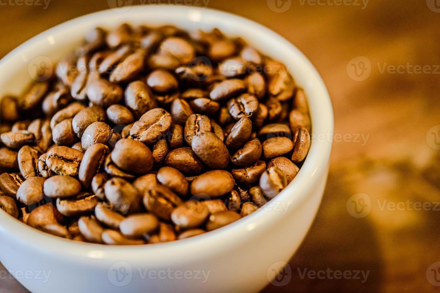 Kaffeebohnen in der Tasse auf grunge Holzhintergrund foto