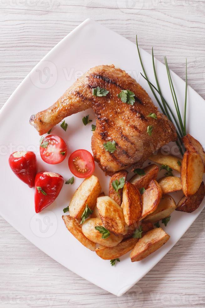 Hähnchenschenkel und Pommes auf einem Teller. Draufsicht vertikal foto