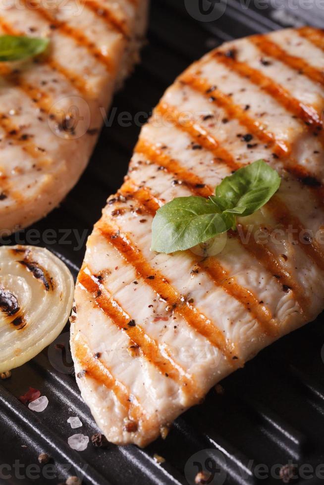 Hähnchenfilet mit Zwiebel auf einem Grillmakro. Vertikale foto