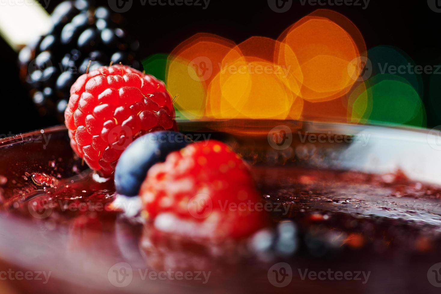 Schließen Sie Glas tropischen Cocktail mit Beeren oder Limonade. foto