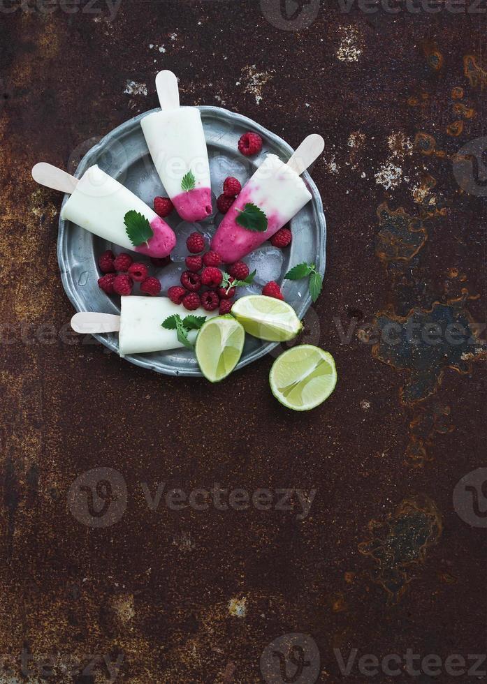 Himbeer-Limetten-Yougurt-Eis oder Eis am Stiel mit frischen Beeren foto