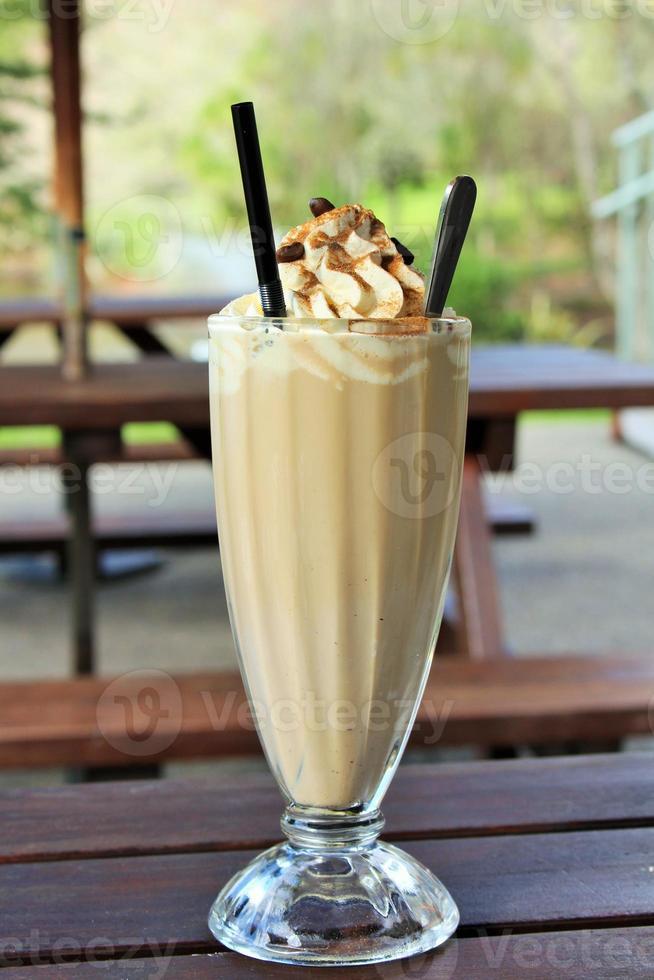 Glas Eiskaffee draußen auf einer Picknickbank foto