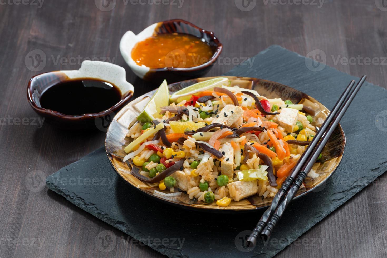 Gebratener Reis mit Tofu, Gemüse und Saucen foto